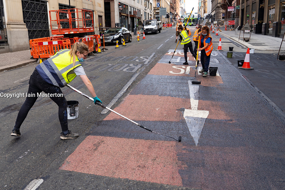 Glasgow, Scotland, UK. 10 July  2021. Workers transforming the centre of Glasgow city centre into a replica of downtown New York City for the new Indiana Jones movie that will be filmed in Glasgow this month. Set decorations include the creation of authentic New York cafes and businesses and the erection of many Stars and Stripes flags. Pic; workers painting over road markings.  Iain Masterton/Alamy Live news.