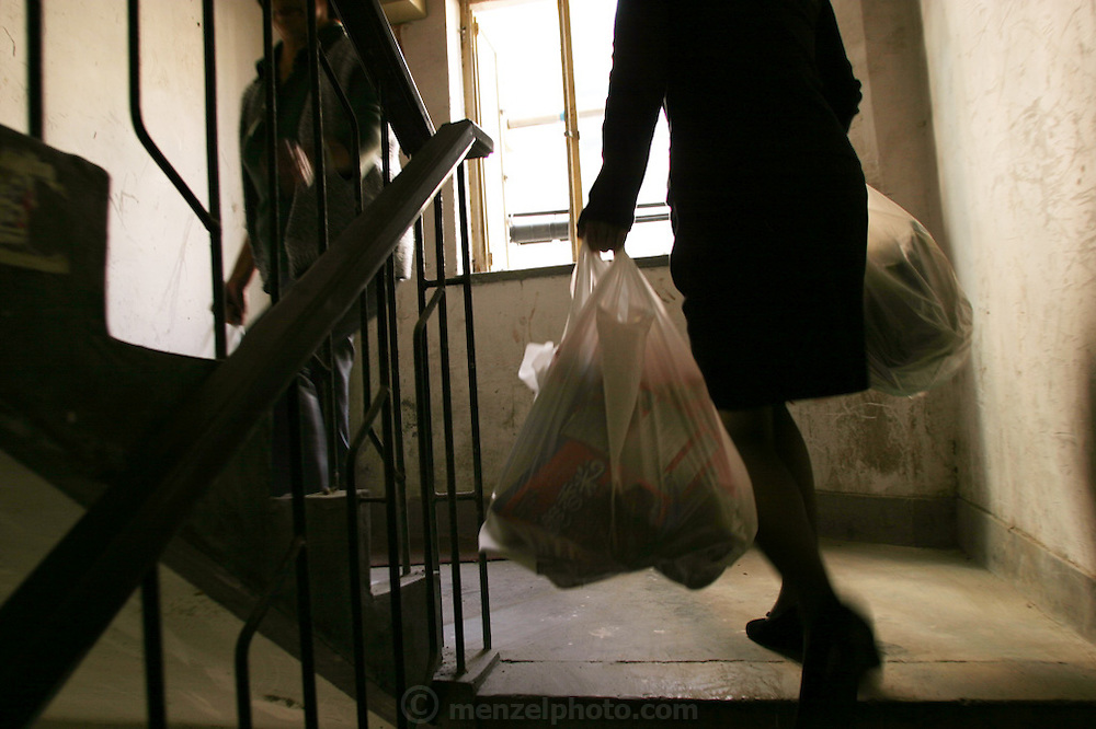 (MODEL RELEASED IMAGE). The Dong family, of Beijing, China, haul their groceries up the stairwell to their newly redecorated fourth-floor flat. Hungry Planet: What the World Eats (p. 81). The Dong family of Beijing, China, is one of the thirty families featured, with a weeks' worth of food, in the book Hungry Planet: What the World Eats.