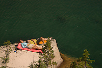 A young couple relaxes on the shoreline of Warbonnet Lake in the Sawtooth Mountains, Idaho.