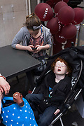 We look down on to a sleeping auburn-haired boy sleeps soundly in his buggy during a daytrip to London. After a long day out with his family, the young lad has clearly had enough of the big city and sleeps soundly with his mouth gaping open. A toy dinosaur peaks from a shopping bag and a woman - perhaps his mother - busily texts from a smartphone.