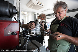 Ron Julian working on his honing machine with Doc Hopkins help in Doc's trailer as he works on Doc's cylinders on rest day during the Motorcycle Cannonball Race of the Century. Dodge City, KS. USA. Sunday September 18, 2016. Photography ©2016 Michael Lichter.