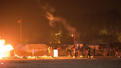 """© Licensed to London News Pictures . 23/10/2016 . Calais , France . Residents set fires at the Calais migrant camp known as """" The Jungle """" , in Northern France , on the evening before the start of the eviction and destruction of the camp . Photo credit: Joel Goodman/LNP"""