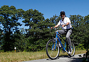 U.S. President Barack Obama rides along a bike path in Correllus State Forest on Martha's Vineyard in West Tisbury, Massachusetts, August 27, 2010. The first family is on a 10-day summer vacation. REUTERS/Jim Young