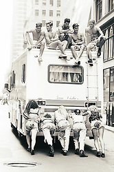 five girls pushing an RV in New York City with five shirtless guys on top of the RV