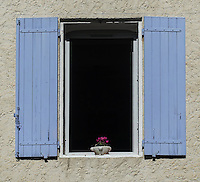 Two periwinkle blue shutters frame a dark  open window with a potted red flower sitting on the windowsill. A grey stucco wall is behind the shutters.
