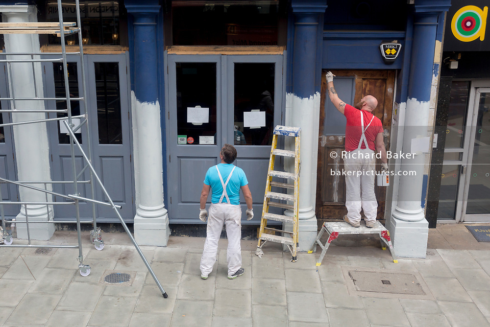 Decorators paint the pillars on the exterior of a pub in Southwark, on 26th March 2019, in London, England