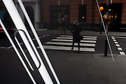A lady pedestrian crosses a zebra crossing with the stripes of an Apple iPhone in the window of John Lewis, London, England.