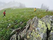 Hikers traverse an open slope in Glacier Peak Wilderness, Washington.