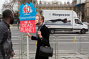 A campaigner wears a Margaret Thatcher face-mask in Parliament Square during the week-long protest by climate change activists with Extinction Rebellions campaign to block road junctions and bridges around the capital, on 23rd April 2019, in London England.