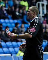 Photo. Glyn Thomas. 08/02/2005.<br /> Reading v Coventry City.<br /> Coca Cola Championship.<br /> Referee G Salisbury holds a bottle which was thrown onto the pitch by a Reading fan.