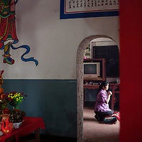 A villager prays to the goddess Mazu at the Wenxing temple.  <br /> <br /> Meizhou is a fishing island and many women pray to Mazu for the safe return of their menfolk. Also, temples dedicated to her were often the first temples erected by seafaring Chinese when arriving in new homeland in thanks for their safe passage.