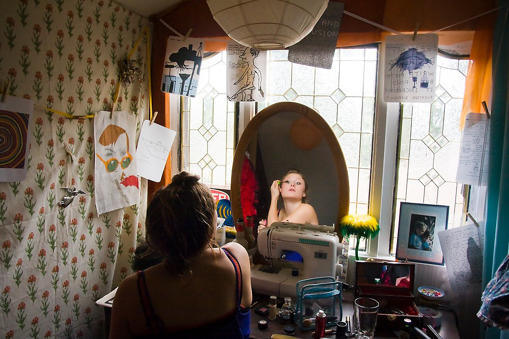 A young woman puts on makeup in her room at home in Seattle, Washington.