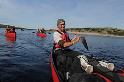 Damian Kailek, 24, from the Dene First Nation paddles in the Thelon Sanctuary August, 2011. It is a place ruled by the biggest and smallest--the grizzly and the mosquito--and by the extremes of sub-arctic seasons. The Thelon is the largest and most remote game sanctuary in North America, which almost no one has heard of. (Photo by Ami Vitale)