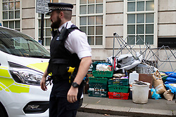 © Licensed to London News Pictures. 07/10/2019. London, UK. A police officer walks past a pile of confiscated equipment after an Extinction Rebellion Roadblock was removed on Millbank . Photo credit: George Cracknell Wright/LNP
