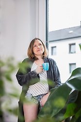 Pregnant woman drinking cup of tea at window, Munich, Bavaria, Germany