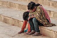 Childhood Misery: A pair of young children hangs their heads in profound misery on the steps of Dashaswamedh Ghat, Varanasi India.