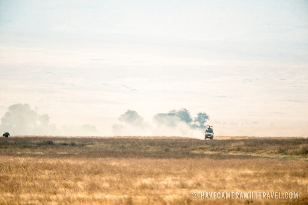 A safari vehicle kicks up dust in the distance at Ngorongoro Crater in the Ngorongoro Conservation Area, part of Tanzania's northern circuit of national parks and nature preserves.