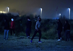 © Licensed to London News Pictures. 23/10/2016. Calais, France. French police confront migrants as they approach the motorway near the 'Jungle' camp in Calais, on the eve of the demolition of the camp. French authorities have given an eviction order to thousands of refugees and migrants living at the makeshift living area of the French coast. Photo credit: Ben Cawthra/LNP
