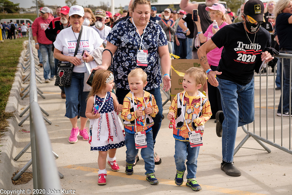 14 OCTOBER 2020 - DES MOINES, IOWA: A woman guides three children into a reelection rally for President Donald Trump. About10,000 people were expected at the Des Moines International Airport for a campaign rally supporting the reelection of President Donald Trump. Trump spoke at the rally, despite testing positive for COVID-19 less than three weeks ago. The rally did not meet the CDC guidelines for a safe gathering in the time of Coronavirus and violated Iowa's health emergency declarations barring gatherings of more than 25 people. This week Iowa exceeded 101,000 cases of COVID-19 and a surge in hospitalizations for COVID-19.        PHOTO BY JACK KURTZ