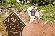 """27 SEPTEMBER 2009 -- PATTANI, THAILAND: Men pray at the graves of family members in Perkuboran To'Ayah Cemetery in Pattani, Pattani, Thailand. Thailand's three southern most provinces; Yala, Pattani and Narathiwat are often called """"restive"""" and a decades long Muslim insurgency has gained traction recently. Nearly 4,000 people have been killed since 2004. The three southern provinces are under emergency control and there are more than 60,000 Thai military, police and paramilitary militia forces trying to keep the peace battling insurgents who favor car bombs and assassination.   PHOTO BY JACK KURTZ"""