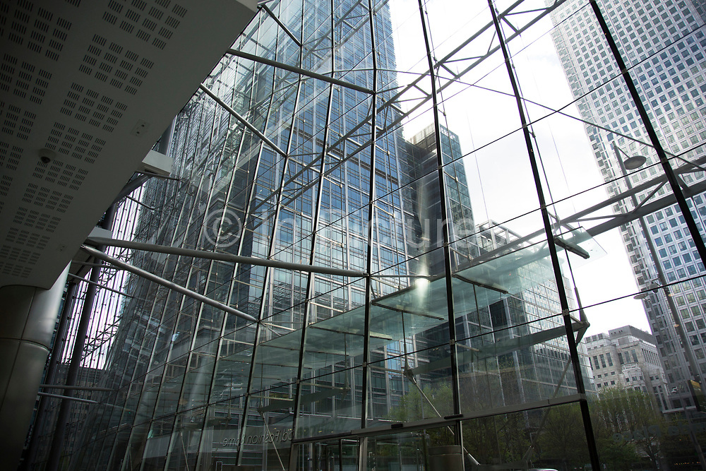 View through the modern architecture of a glass building looking towards Canary Wharf in London, England, United Kingdom.