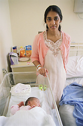 Young mother standing next to new born baby in cot on Maternity ward of hospital,
