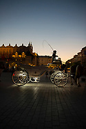 A Polish woman sits in her horse-drawn carriage in Krakow's Rynek Glowny square at dusk, waiting for a fare. The carriages are popular with tourists.