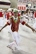 Brazilian man in costume smiling at the camera. Grande Rio Samba School from the Special Group, practices their Carnival procession in the Sambadrome, Rio de Janeiro, Brazil