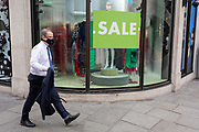 On the day that covid pandemic guidelines for shoppers in England mean that the wearing of face coverings in shops becomes mandatory, a man wearing a face mask passes Harvey Nichols in Knightsbridge, on 24th July 2020, in London, England.