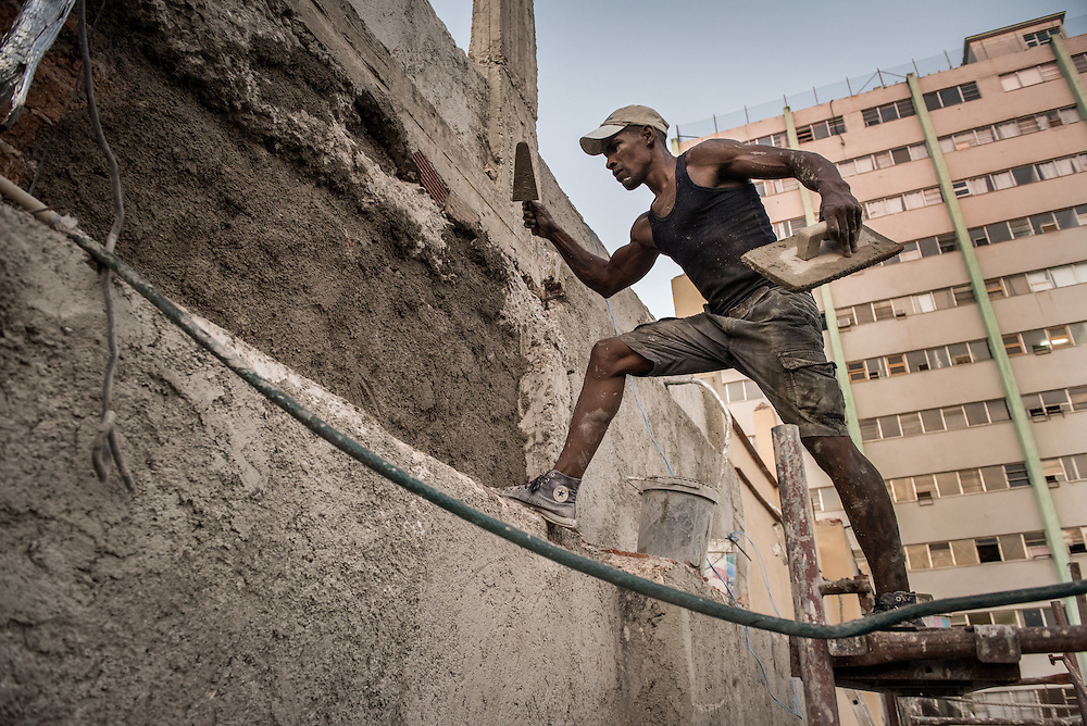 Osmar Rivero DeEspaigne, 35, applies cement to the side of a building during reconstruction January 2, 2015 in Old Havana, Cuba. The United States announced last month that it will end its fifty-year trade embargo with Cuba and move to normalizing relations. Cuba's budding private sector is strengthening, but still has a long way to go to prepare for the expected stream of tourists. Photo Ken Cedeno