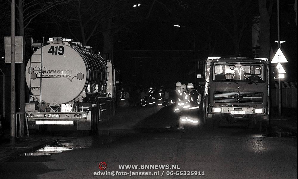 NLD/Hilversum/19900306 - Lekkende vrachtwagen met chemicalien J.v.d.Heijdenstraat Hilversum, weg word gereinigd door de brandweer