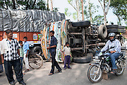 People are passing by a capsized Tata truck on a rural road outside of Varanasi, Uttar Pradesh, India.