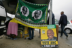 Wednesday 8th May 2019.<br /> Sinenjongo High School, Joe Slovo Park,<br /> Milnerton, Cape Town, <br /> Western Cape, <br /> South Africa.<br /> <br /> SOUTH AFRICAN GENERAL ELECTIONS 2019!<br /> <br /> SOUTH AFRICAN PROVINCIAL AND NATIONAL ELECTIONS 2019! <br /> <br /> An ANC political party members representatives table shows much activity as a printed cloth shows the image of Nelson Mandela and the official ANC logo, colours and emblems and an ANC election poster with the face of South African President Cyril Ramaphosa on it leans against a tent pole outside the voting station at Sinenjongo High School, Joe Slovo Park near Milnerton, Cape Town, Western Cape, South Africa.  <br /> <br /> Registered South African Voters head to the various IEC (Independent Electoral Commission) Voting Stations where they are registered to vote as they cast their votes and take part in voting and other activities on Voting Day 8th May 2019 during the South African General Elections 2019. Voters from across the nation stood in queue's along with many others to vote in the Provincial and National Elections being held in South Africa on Wednesday 8th May 2019.   <br />  <br /> Copyright © Mark Wessels. All Rights Reserved. No Usage Without Permission.<br /> <br /> PICTURE: MARK WESSELS. 08/05/2019.<br /> +27 (0)61 547 2729.<br /> mark@sevenbang.com<br /> studioseven@mweb.co.za<br /> www.markwesselsphoto.com