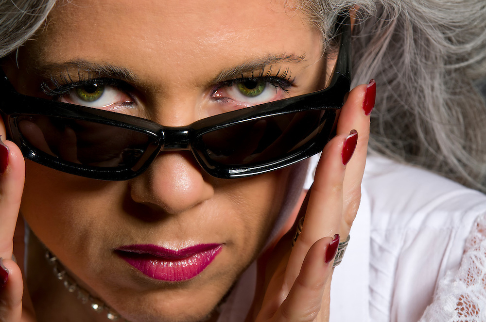 Attractive woman in her fifties looking over sunglasses