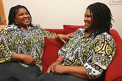 Identical twins sitting together on sofa laughing.