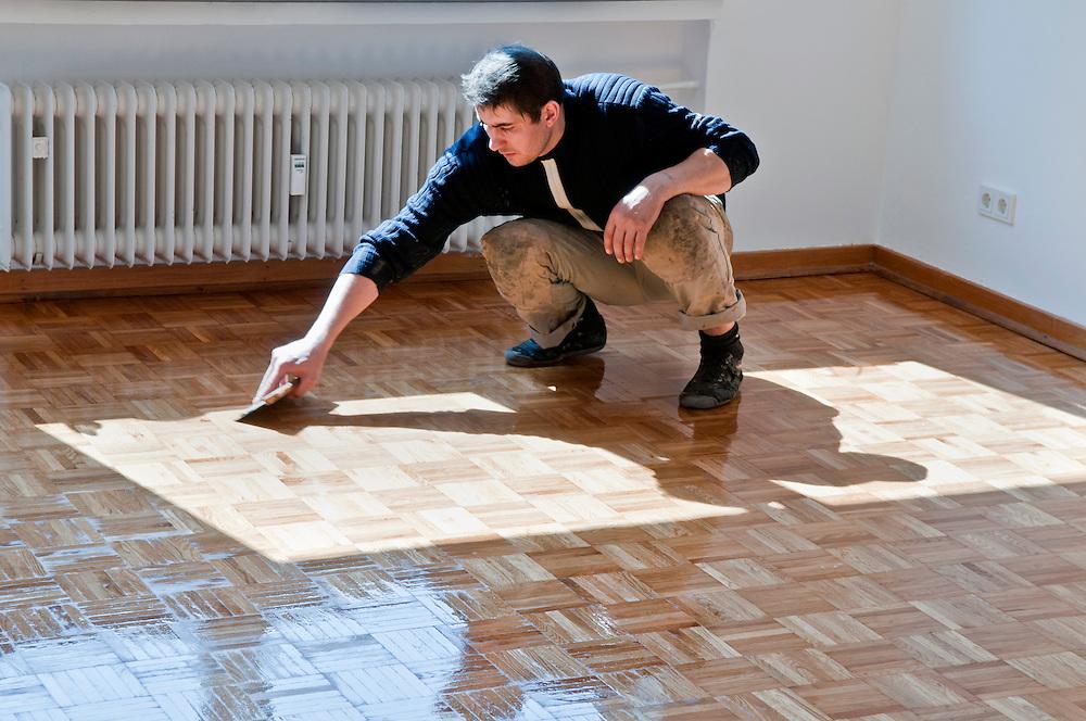 Ein Handwerker trägt verteilt eine Ölschicht zur Versiegelung eines Parkettbodens  |  worker prepares a wooden floor, A craftsman carries a layer of oil distributed to seal a parquet floor  |