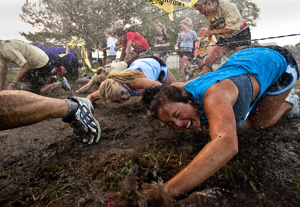 Prairie sludge trudge participants started by crawling under a fence as a sprinkler created a muddy puddle at the Stuhr Museum. Over 800 participated in the 2.5 or 7.5 mile obstacle run, the first of it's kind for the museum, which lead contestants through water, mud, and and grass. All proceeds from the event go to the Grand Island Salvation Army and Stuhr Museum.