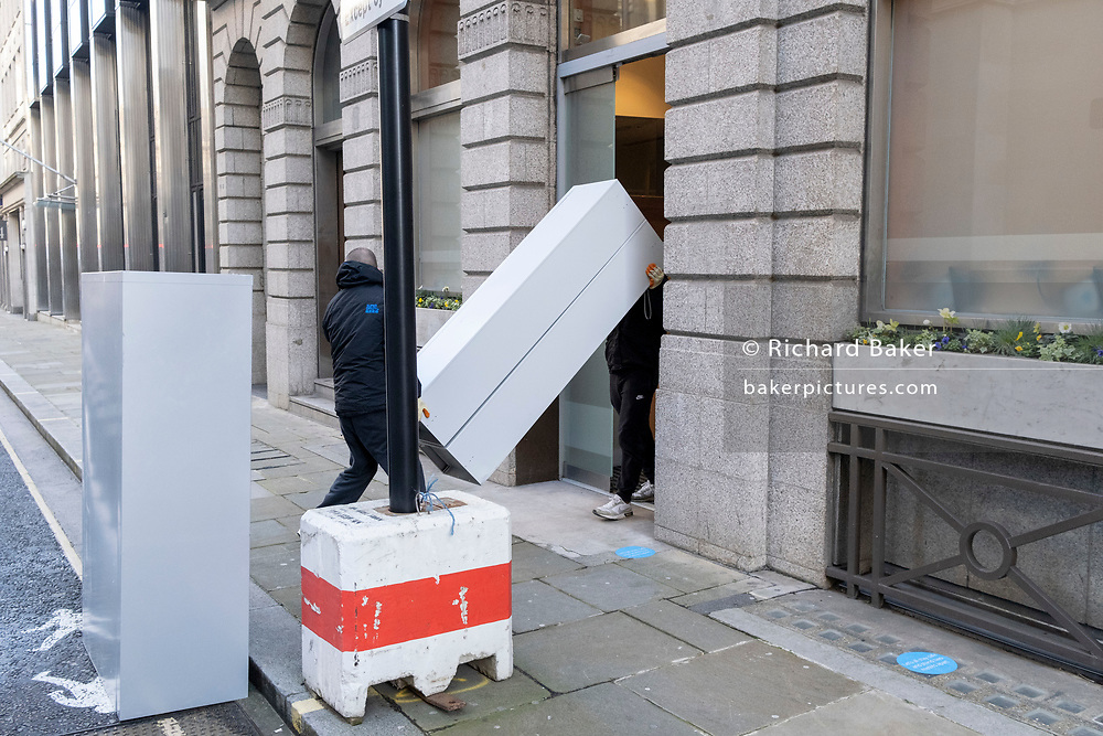 In a deserted street, contractors remove office locker furniture from a nearby building during the third lockdown of the Coronavirus pandemic, in the City of London, the capital's financial district, on 10th February 2021, in London, England.