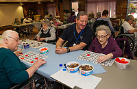 Volunteer Coordinator Randy MacDonald plays a game of BINGO alongside Marcelle Smith Tuesday afternoon at the Belknap County Nursing Home.  (Karen Bobotas/for the Laconia Daily Sun)