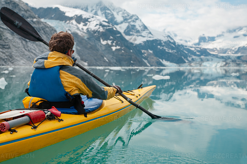 A man paddling a yellow sea kayak in Johns Hopkins Inlet in Alaska's Glacier Bay National Park and Preserve. Photo © Robert Zaleski / rzcreative.com<br /> —<br /> To license this image contact: robert@rzcreative.com