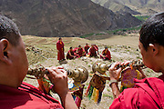Monks blow horns as they prepare for prayer on a mountain above a monastery in the Tibetan Plateau.