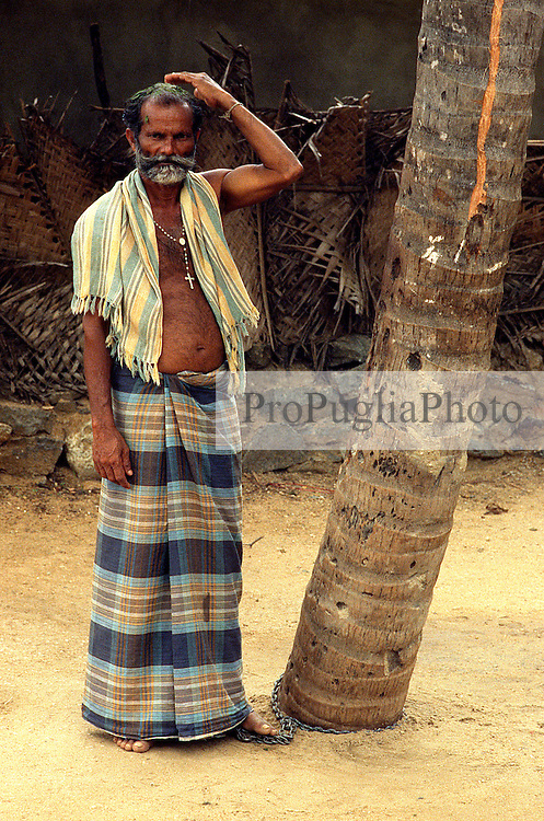 TAMIL NADU, MARCH 1994.A man who is chained to a tree is looking at the camera. He is wearing a rosary around his neck.