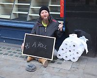 Homeless man selling loo rolls for £1 each  on the Strand High Street , London photo by Roger Alarcon