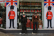 A tourist trinket shop in Oxford Street, central London. Looking across the pavement towards the shop window, we see one of the tacky styles of retailers in the capital, home to many international brands but also more downmarket displays of items for the tourist trade including the British guardsman solder in ceremonial uniform and busby bearskin headwear. red telephone boxes (largely unused nowadays by Londoners because of personal smartphone ownership), Big Ben models, mugs and bears contunue to appear on shelves for those wanting overpriced trinkets to take home.