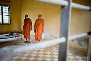 14 MARCH 2006 - PHNOM PENH, CAMBODIA: Buddhist monks walk through a former torture chamber in a Khmer Rouge torture center in Phnom Penh, Cambodia. In the three years, eight months and 20 days that the KR controlled Cambodia, they massacred more than 2 million people in a bloodletting that did not stop until the Vietnamese invaded Cambodia and ousted the KR regime. The KR started by murdering anyone who had an education, like teachers, technocrats the intelligentsia, and monks and eventually started killing members of their own movement they suspected had deviated from the movement's path.  Photo by Jack Kurtz / ZUMA Press
