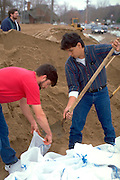 Men age 25 making sand bags for flooded St Croix River.  Stillwater  Minnesota USA