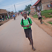CAPTION: John has a hearing impairment, but benefited from Signhealth Uganda's projects in Lukaya and has since regained most of his hearing function. From school, he has to walk about four kilometres through the town of Lukaya and the bush in order to reach his home village of Lusango. Without shoes, the journey is arduous; his skin's constant contact with the ground also impacts on his personal hygiene, a factor in causing hearing impairment through ear infections. LOCATION: Lukaya Town, Kalungu District, Central Region, Uganda. INDIVIDUAL(S) PHOTOGRAPHED: John Makumbi.