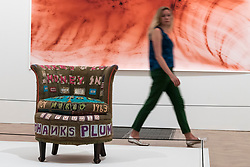 "© Licensed to London News Pictures. 05/06/2018. LONDON, UK. A staff member views ""There's a Lot of Money in Chairs"", 1994, by Tracey Emin in front of ""Greifbar 1"", 2014, by Wolfgang Tillmans at a preview of the 250th Summer Exhibition at the Royal Academy of Arts in Piccadilly, which has been co-ordinated by Grayson Perry RA this year.  Running concurrently, is The Great Spectacle, featuring highlights from the past 250 years.  Both shows run 12 June to 19 August 2018.  Photo credit: Stephen Chung/LNP"