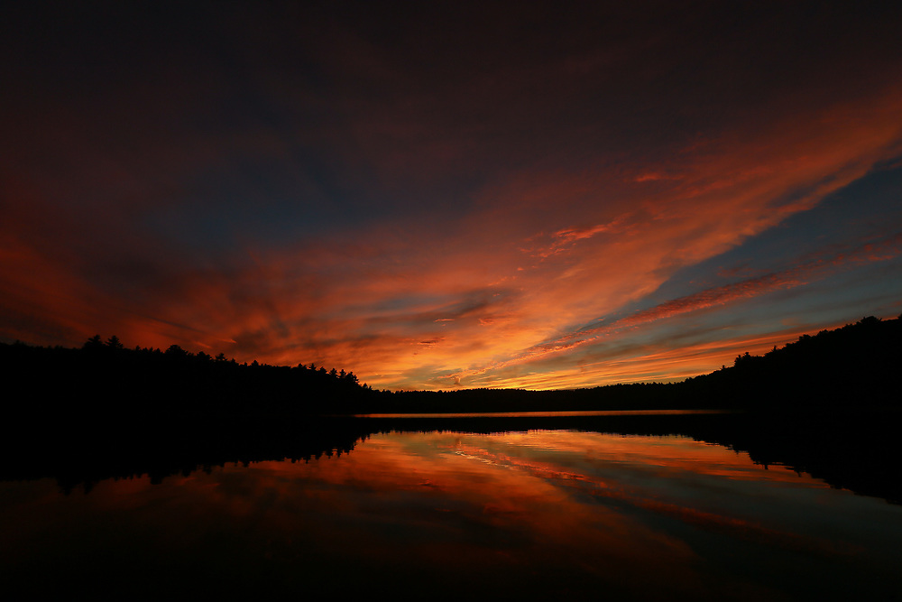 A fiery sunset reflecting on the calm waters of Walden Pond.