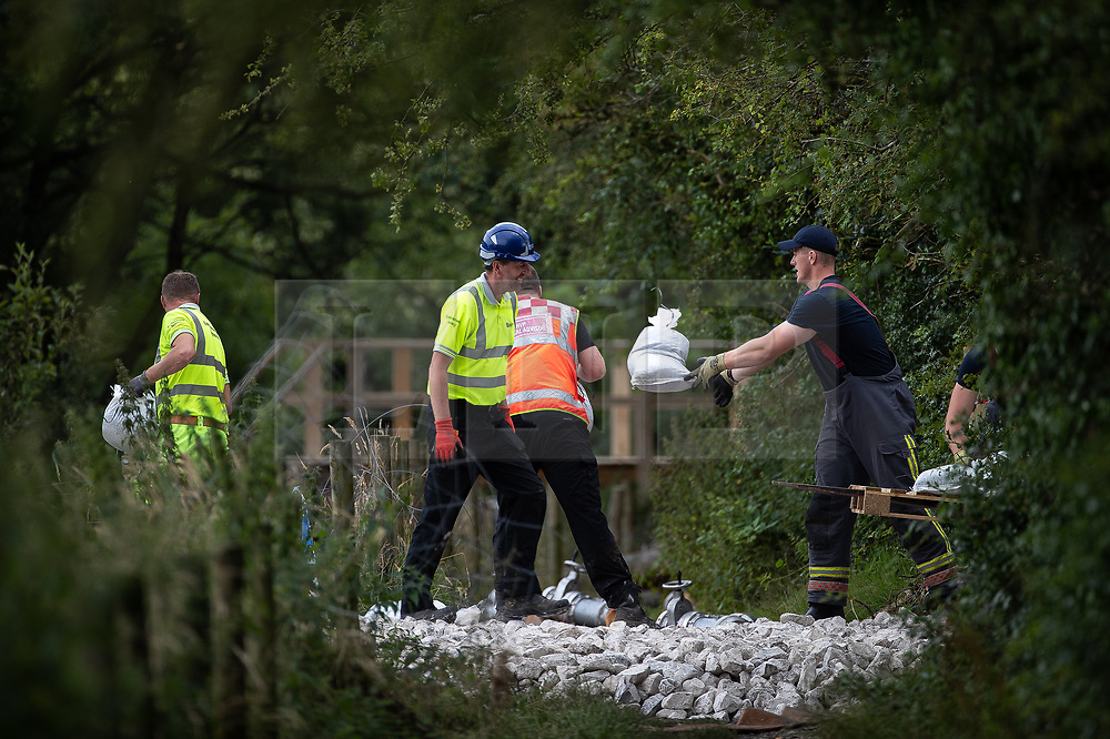© Licensed to London News Pictures. 04/08/2019. Whaley Bridge, UK.  Sandbags are handed between emergency workers at a pumping station adjacent to the reservoir as efforts continue to lower the water level . More rain is forecast today (Sunday 4th August) in the town of Whaley Bridge in Derbyshire after earlier heavy rain caused damage to the Toddbrook Reservoir , threatening homes and businesses with flooding. Photo credit: Joel Goodman/LNP